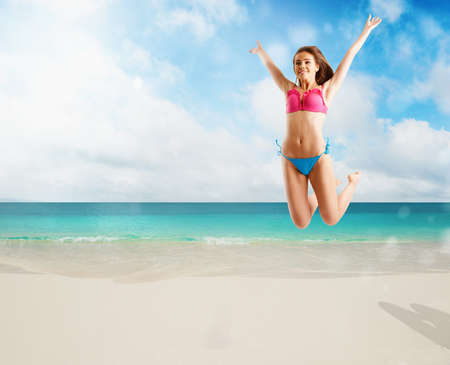 Woman in bikini swimsuit jumping from joy on tropical beach
