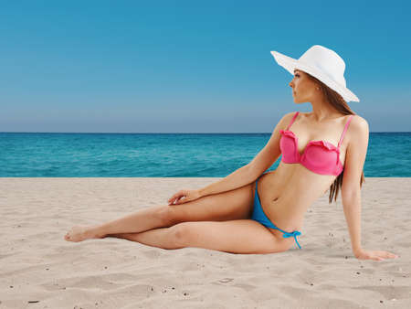 Girl in bikini sunbathing on beach Фото со стока