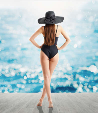 Woman in elegant black hat and swimsuit looks at sea