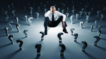 Businessman with many question marks. Concept of failure and problem photo