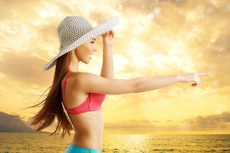 Woman at tropical beach looks at horizon for new travel route Stock Photo