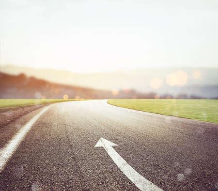 Carretera con signo de flecha en el asfalto con sol en el frente. Concepto