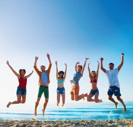 幸せの笑みを浮かべて友達がビーチでジャンプ