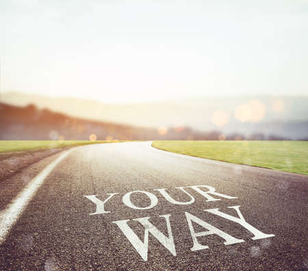 Road with your way writing on the asphalt with sun in front