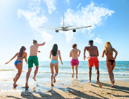 Group of friends run to the sea with an aircraft in the sky. Concept of travel and summer Stock Photo