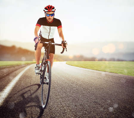 Front view of a road cyclist in uniform during a race at sunset