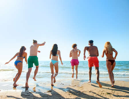 Group of friends run to the sea. Concept of summertime Stock Photo