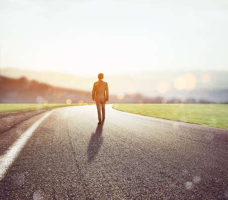 lejos: El hombre camina por un camino desconocido para una nueva aventura
