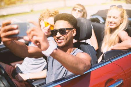 Jonge vrienden nemen een selfie in een cabrioletauto Stockfoto