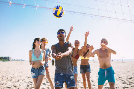 Group of friends playing at beach volley at the beach Stock Photo