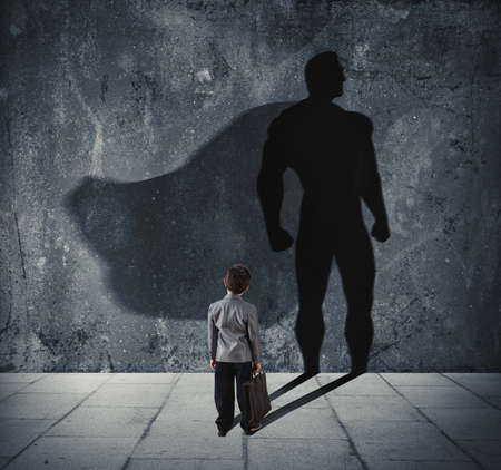 Young businessman with his shadow of super hero on the wall. Concept of powerful small man photo