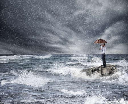 海の嵐の中傘を持ったビジネスマン。保険保護の概念