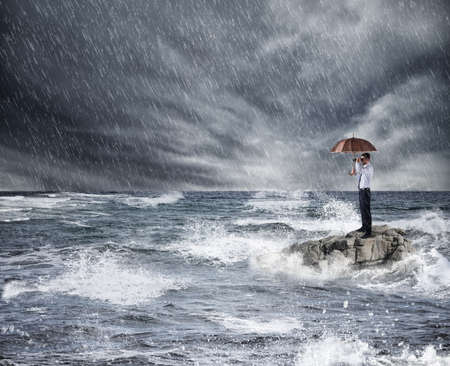 Businessman with umbrella during storm in the sea. Concept of insurance protection Banco de Imagens