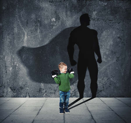 Young child with his shadow of super hero on the wall. Stock Photo