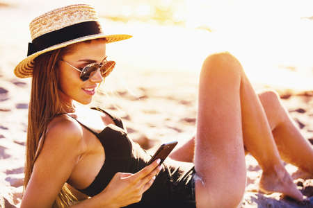 Beautiful girl sends a message with her smartphone at the beach