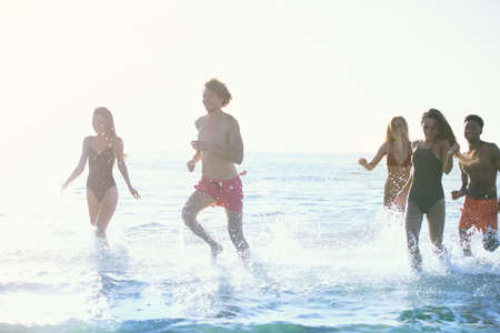 drop water: Group of friends run in the sea. Concept of summertime