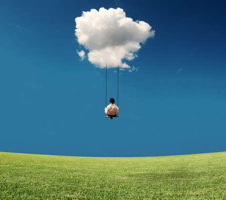 Carefree businesswoman on a swing attached in a cloud Stock Photo