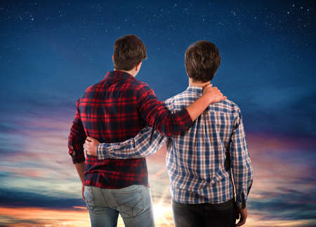 Two friends hugging each other looking at the sky.