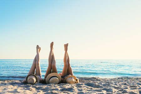 Groep gelukkige vrienden met plezier op oceaanstrand bij dageraad met benen omhoog
