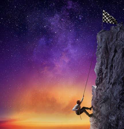 Zakenman een berg beklimmen om de vlag te krijgen. Prestatie business doel en moeilijk carrière begrip Stockfoto