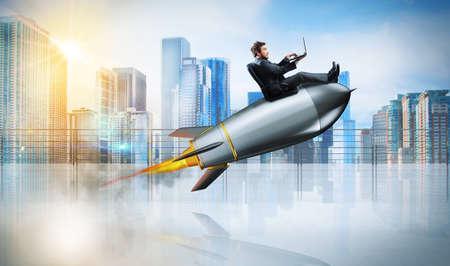 Conceito de internet rápida com um empresário com laptop sobre um foguete Foto de archivo - 84255496