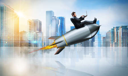 Fast internet concept with a businessman with laptop over a rocket photo