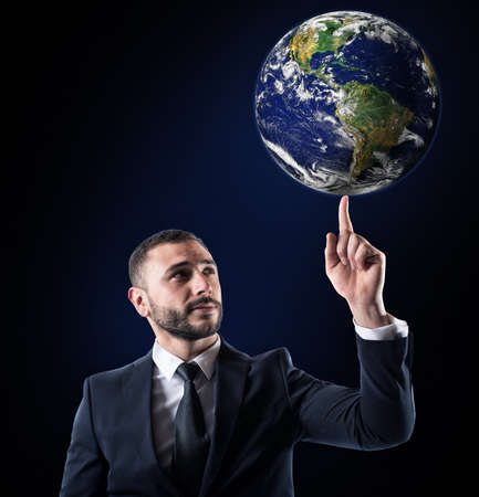 Businessman holds the world with a finger. World provided by NASA Stock fotó