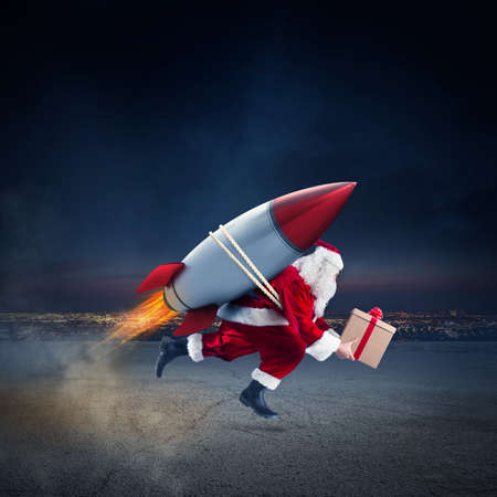 Santa Claus with gift box ready to fly with a rocket in the sky Stock fotó - 84555377