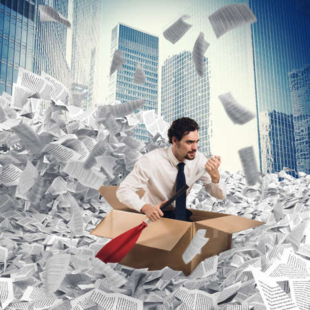 Businessman extricate himself from a sea of paper Reklamní fotografie