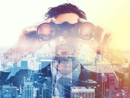 Hombre de negocios mirando hacia el futuro con binoculares Foto de archivo - 85120563