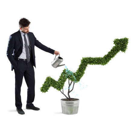 Zakenman die een plant met een vorm van pijl watert. Concept groeiende bedrijfseconomie. Stockfoto