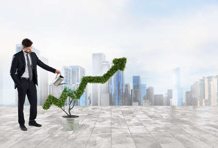 Businessman that watering a plant with a shape of arrow. Concept of growing of company economy . Standard-Bild