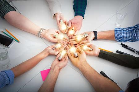 Teamwork- und Brainstorming-Konzept mit Geschäftsleuten, die eine Idee mit einer Lampe teilen. Konzept des Starts Standard-Bild