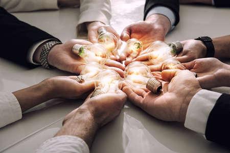 Koncepcja pracy zespołowej i burzy mózgów z biznesmenami, którzy podzielają pomysł z lampą. Koncepcja uruchomienia