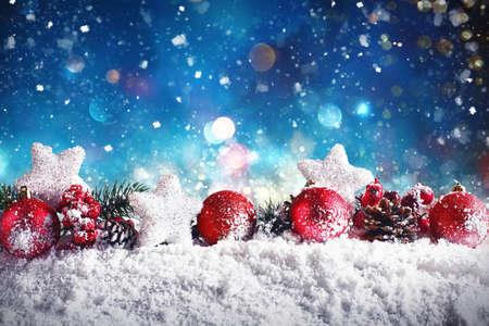Kerstmissamenstelling met ballen, sterren en slingers op sneeuw met nachtlicht Stockfoto