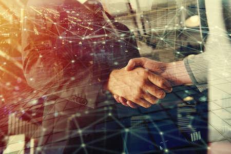 Händeschütteln-Geschäftsperson im Büro mit Netzeffekt. Konzept der Teamarbeit und Partnerschaft. Doppelbelichtung