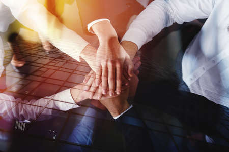 Business people joining hands in a circle in the office. concept of teamwork and partnership. double exposure