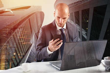 Geschäftsmann arbeitet mit Smartphone und Laptop