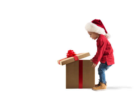 Child that open a magic Christmas gift. White background Stockfoto