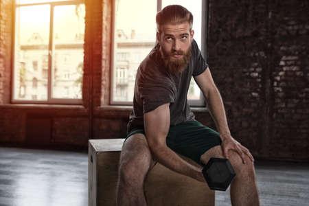Athletischer Mann trainiert Bizeps in der Turnhalle