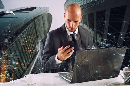 Businessman works with smartphone and laptop Standard-Bild