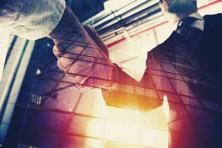 Handshaking business person in office. concept of teamwork and partnership. double exposure Standard-Bild