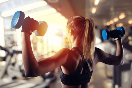 Atletische gespierde vrouw traint biceps met halters in de sportschool