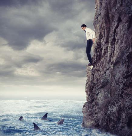 ビジネスマンはサメと一緒に海に落ちる可能性が高いです。リスクと困難の概念