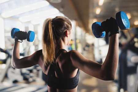 Athletic girl trains biceps at the gym