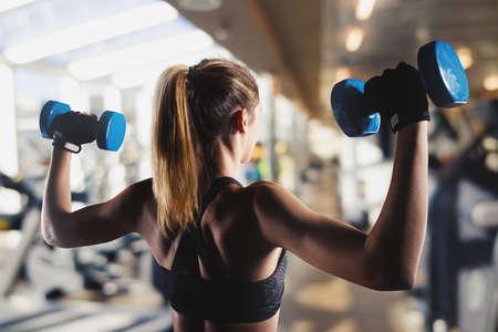 Atletisch meisje traint biceps in de sportschool