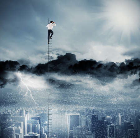 Businessman on a ladder escapes from crisis and looking for a new way Stock Photo