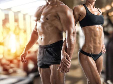 Muskulöser Mann und Frau in der Turnhalle Standard-Bild - 93481914
