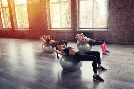 Mädchen, die an einer Turnhalle mit dem Gymball ausarbeiten Standard-Bild - 94189899