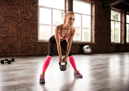 Blonde girl working out at the gym with a kettlebell. crossfit exercise Stock Photo